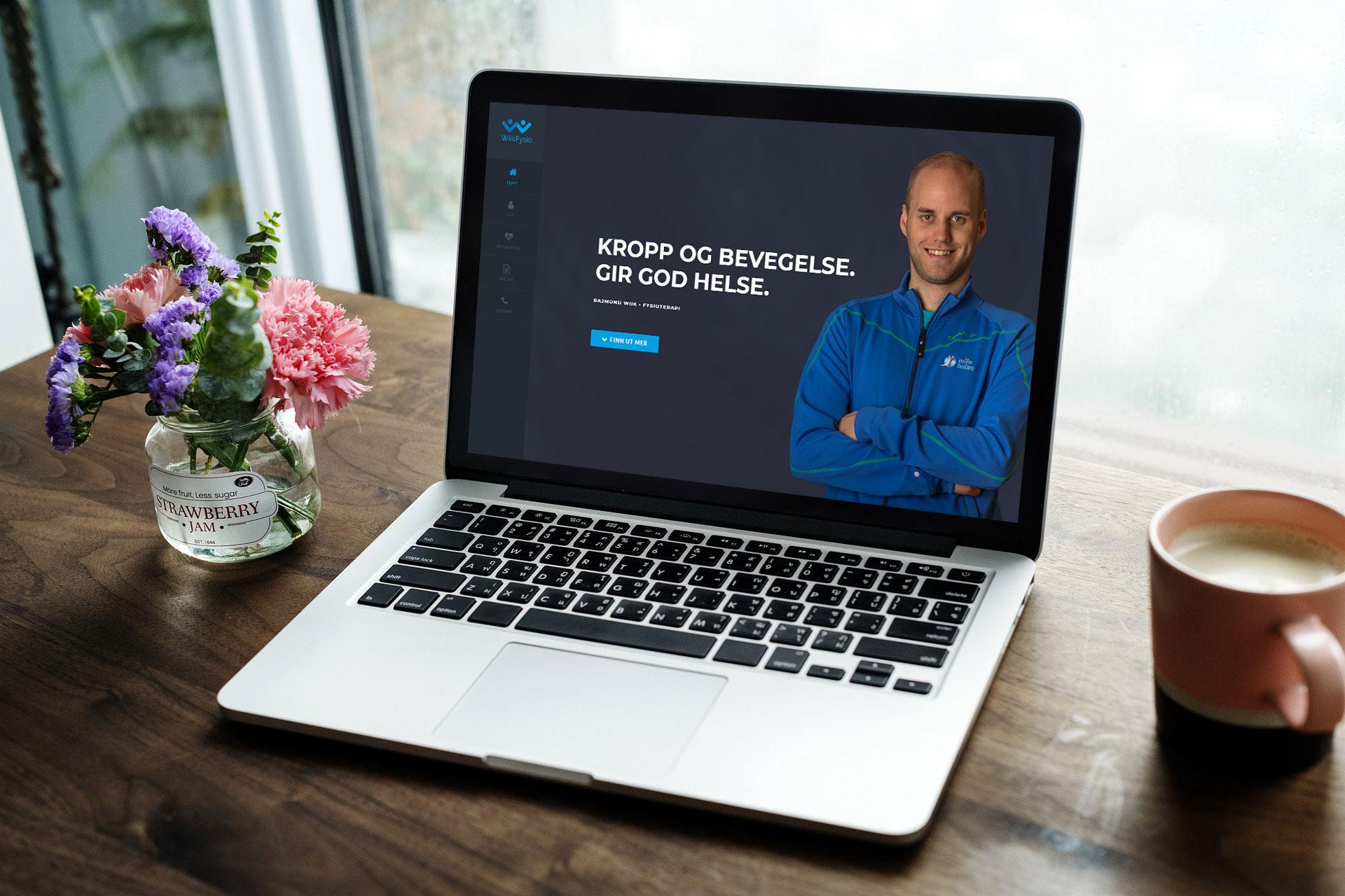 En ryddig pult med kaffe kopp, blomsterpotte og en laptop med wiikfysio sine nettsider.