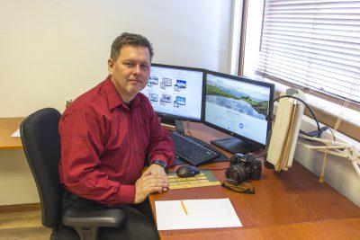 Trond Larsen sitter ved skrivebord med dataskjermeri bkgrunnen. På bordet er skriveblokk og fotoapparat.