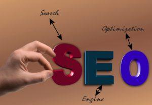 Bokstavene S, E og O med tekster som henleder til Search Engine Optimization. En hånd kniper tak i S med peke og tommelfinger.